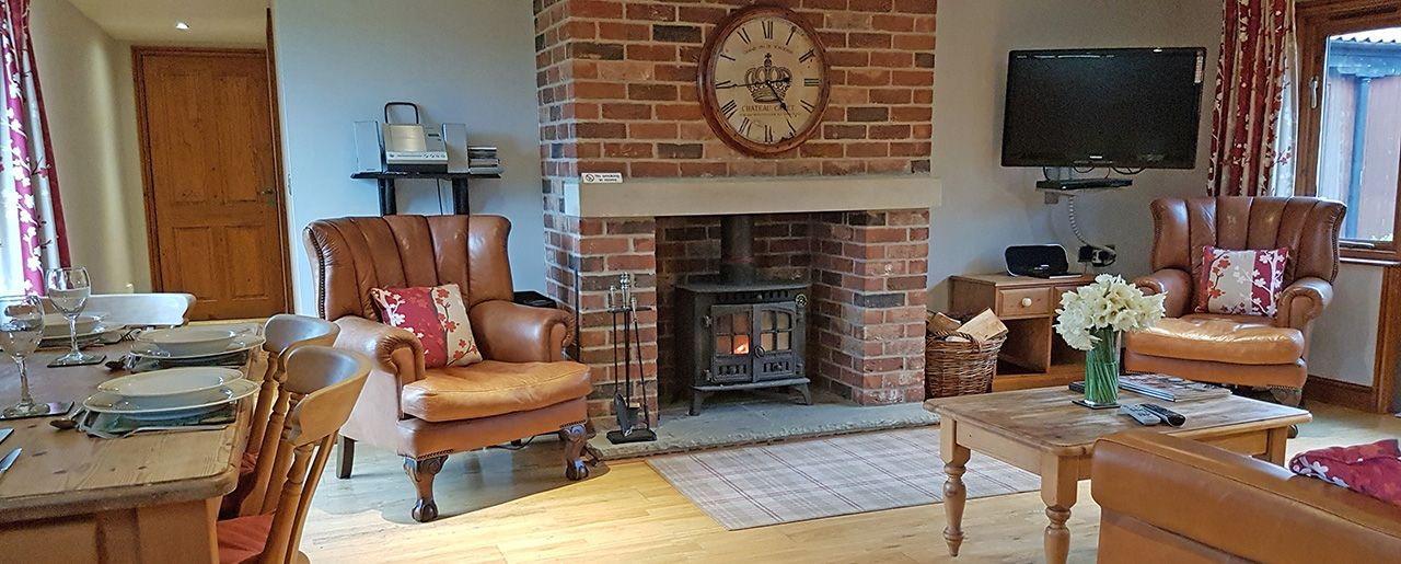 Places to stay in Lincolnshire, Elm cottage with soft leather sofa and chairs in the lounge.